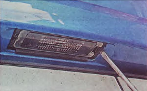 Тонкой шлицевой отверткой отжимаем фиксатор и извлекаем фонарь освещения номерного знака из бампера.
