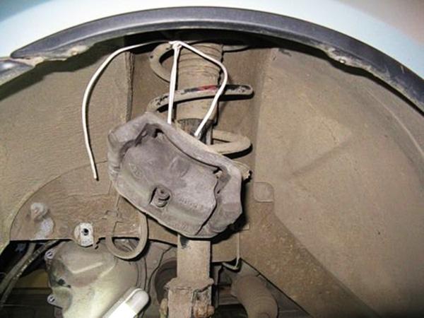 Переходим к левому переднему колесу и откручиваем тормозной суппорт.